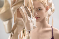 Ballet dancer and pointe shoes. Blonde ballerina stands between hanging beige pointe shoes on the light background in the studio. She wears a violet top and stock photos