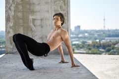 Ballet dancer posing at unfinished building. Topless ballet dancer is posing on the concrete floor of the unfinished building on the cityscape background. He Stock Photography