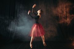 Ballet dancer in red dress dancing on the stage. In theatre. Graceful ballerina training in class Stock Photos