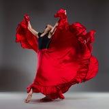 Ballet dancer in red dress. Full length studio shot on gray background royalty free stock images