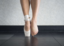 The ballet dancer`s balance on their pointe shoes, and the feet behind them. The ballet dancer balance on their pointe shoes, and the feet behind them- the fine stock images