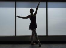 Ballet dancer Silhouette in a Window frame. Framed silhouette of a ballet dancer in the window of a dance studio Stock Image