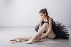 Ballet dancer in beautiful dress. Ballet dancer sitting on the floor and prepare for exercise royalty free stock photo