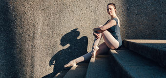 Ballet dancer sitting on stairs wearing pointe shoes. Stock Images