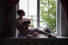 Ballet dancer sitting on windowsill holding Royalty Free Stock Photo