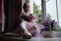Ballet dancer sitting on windowsill holding Stock Image