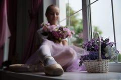 Ballet dancer sitting on windowsill holding Stock Image