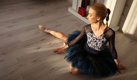Ballet dancer sitting on the wooden floor. Female ballerina having a rest. Ballet concept. royalty free stock images