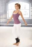 Ballet dancer standing at bar Stock Images