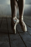 Ballet dancer standing on the tiptoes in the black room Stock Photos