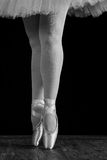 A ballet dancer standing on toes while dancing on black background Royalty Free Stock Photography