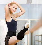Ballet dancer stretches herself near barre Royalty Free Stock Image