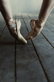 Ballet dancer stretching on tiptoes in the black room Stock Images