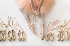 Ballet dancer in studio. Ballerina sits on the white floor and holds a beige pointe shoe in the studio. She wears a light dance wear and a peach tutu. On the Stock Images