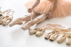 Ballet dancer in studio. Woman who is ballerina sits on the white floor and dresses a beige pointe shoe in the studio. She wears a light dance wear and a peach Royalty Free Stock Image
