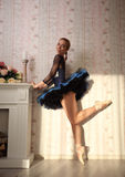 Ballet dancer in sun light in home interior, standing on one leg. Portrait of a professional ballet dancer in sun light in home interior Stock Photo