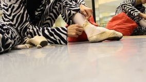 Ballet dancer tie shoes, ready for ballet practice stock video footage