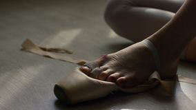 Ballet dancer tie up her pointes. Ballet dancer tying ballet shoes before training Stock Image
