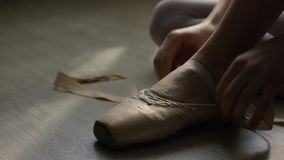 Ballet dancer tie up her pointes. Ballet dancer tying ballet shoes before training Royalty Free Stock Photos