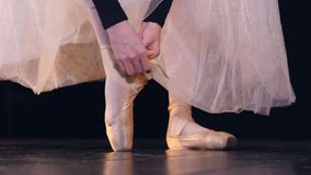 A ballerina straps her ballet shoes laces on her ankle. A ballet dancer ties her pearl colored shoes with ribbons stock video footage