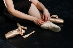 Ballet-dancer ties up pointe shoes. no face. back. girl royalty free stock image