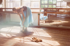 Ballet dancer tying ballet shoes. Young ballerina or dancer girl putting on her ballet shoes. Girl in a turquoise ballet skirt. Old ballet shoes on old wooden royalty free stock photos