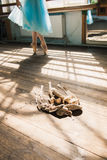Ballet dancer tying ballet shoes. Young ballerina or dancer girl putting on her ballet shoes. Girl in a turquoise ballet skirt. Old ballet shoes on old wooden stock photos