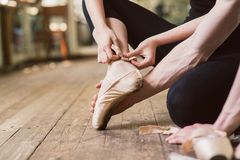 Ballet dancer tying ballet shoes royalty free stock image
