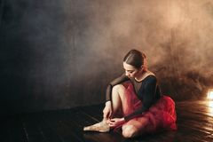 Ballet dancer tying pointe shoes Royalty Free Stock Image