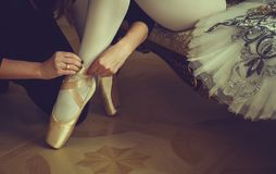 Ballet dancer tying ballet shoes. close-up. Ballet dancer tying ballet shoes stock photo