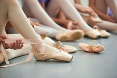 Ballet dancer tying ballet shoes. royalty free stock photography