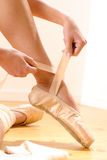 Ballet dancer tying slippers around her ankle Royalty Free Stock Images
