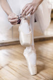 Ballet dancer tying slippers around her ankle