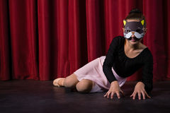 Ballet dancer wearing mask crawling. Through the stage curtain stock photo