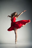Ballet dancer wearing red dress over grey Royalty Free Stock Image