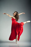 Ballet dancer wearing red dress over grey. Gorgeous young ballet dancer wearing red dress over dark grey background royalty free stock images
