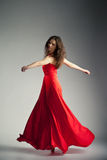 Ballet dancer wearing red dress over grey Royalty Free Stock Photography