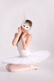 Ballet dancer in a white tutu and a carnival mask Stock Photos