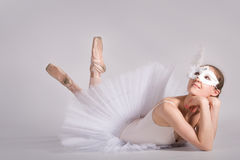 Ballet dancer in a white tutu and a carnival mask Stock Photo