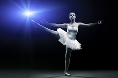 Ballet dancer in white tutu posing on one leg stock photo