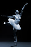 Ballet dancer in white tutu posing on one leg royalty free stock photos
