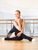 Ballet dancer works out sitting on the wooden floor Stock Images