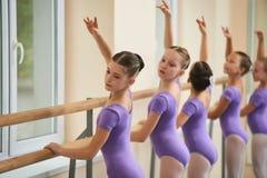 Ballet dancers doing exercises at ballet barre. Young cute ballerina perform ballet element in studio. Ballet dance education Royalty Free Stock Images
