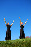 Ballet dancers in field. Two young ballet dancers in black dresses in countryside field with blue sky background Royalty Free Stock Photo