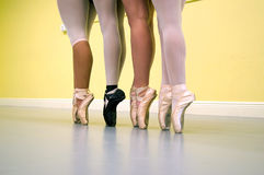 Ballet dancers legs on pointe. Four ballerinas are standing on their toes, on pointe, wearing ballet shoes and tights of various types during dance class stock image