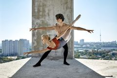 Ballet dancers posing at unfinished building. Amazing couple of ballet dancers posing on the concrete floor of the unfinished building on the cityscape Stock Photos