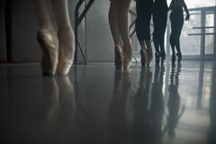 Ballet dancers stands by the ballet barre. Stock Photo