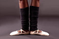 Ballet feet first position. Feet of a ballerina in the first ballet position: white pointes, black socks and grey background Royalty Free Stock Photo