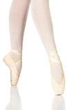Ballet Feet Positions. Young female ballet dancer showing various classic ballet feet positions on Pointe against a white background - 4th position en pointe stock image