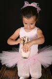 Ballet girl. Cute brunette ballet girl looking into a pointe shoe Royalty Free Stock Photos